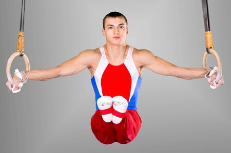 The sportsman the guy, carries out difficult exercise, sports gymnastics