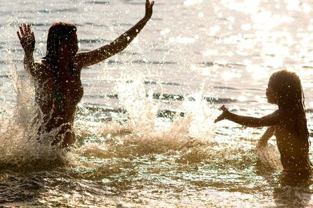 gaily: the silhouette family gaily splashes in water, outdoor, evening or morning