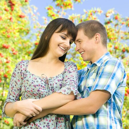 Young beautiful girl and the guy, embrace under a bush of a mountain ash, a happy smile.  Adobe RGB (1998) photo
