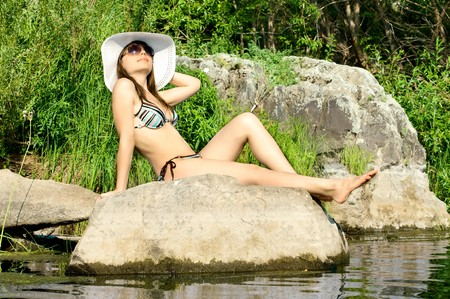 sexy slenderness beautifully sit on rock, outdoor with  bonnet, sun day photo