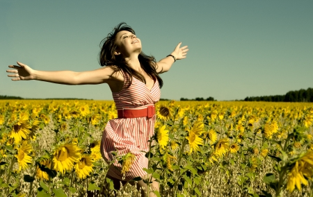 The young beautiful woman quickly runs on a glade of sunflower, smiles, hands are opened  Stock Photo - 7717640