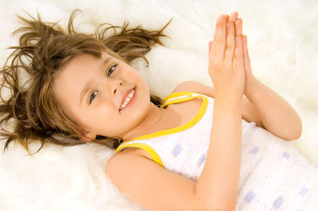 downwards: Beautiful, small the girl lays a stomach downwards on white to fur, smiles Stock Photo