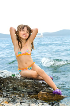 little girl swimsuit: pleasure beautiful little girl sit on calculus, on coast, in  swimsuit and smile