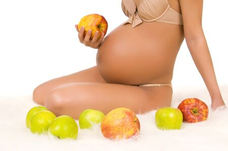 body pregnant woman with very big stomach, hand hold aple Stock Photo - 7701989