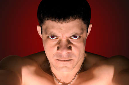 delinquent: very angry man, face close up, red background gradient, horizontal image Stock Photo