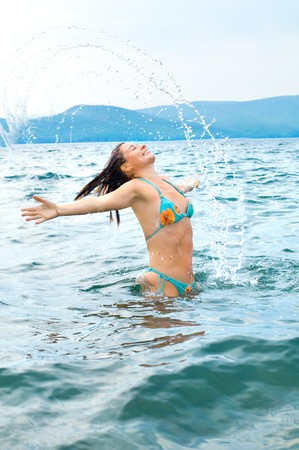 gaily: the pretty woman gaily splashes  waist-deep in water, outdoor, and smile