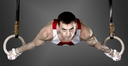 koncentrace: The sportsman the guy, carries out difficult exercise, sports gymnastics