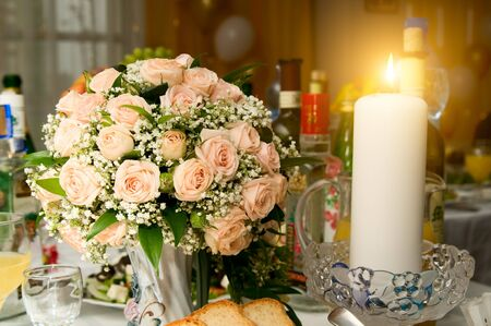 the Candles and wedding bouquet roses on a banquet table, beautifully  brightly burn