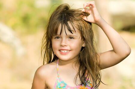 zerzaust: Die kleinen sch�nen M�dchen mit nassen zerzausten langen Haaren, in einem sonnigen Tag im Freien.