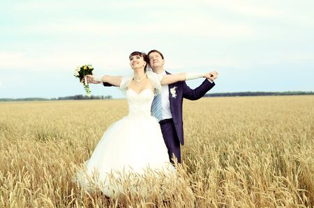 necking: cutie happy married  couple  on nature, on wheaten field,  embrace and smile Stock Photo