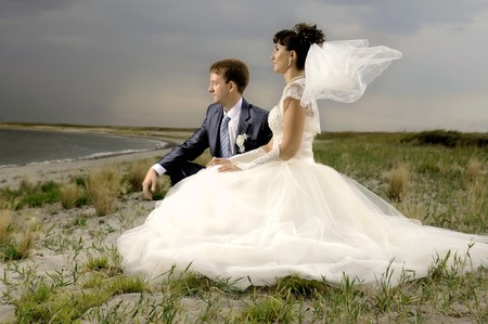 impassioned: the beauty happy married  couple sit on coast, puff wind, imminent  storm-cloud