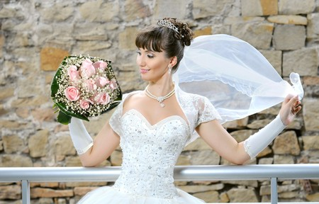 fiancee: The young beautiful  happy fiancee,  with cutie wedding bouquet,  smile...