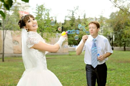 cutie:  cutie happy married  couple  on nature in park ,  play with soap-bubble and joy smile