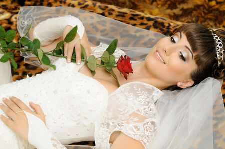 fiancee: The young beautiful  happy fiancee,  lie,  hold rose in hands and smile Stock Photo