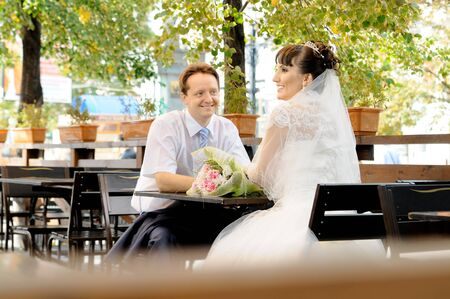 cutie: the cutie happy married couple sit in restaurant street, smile
