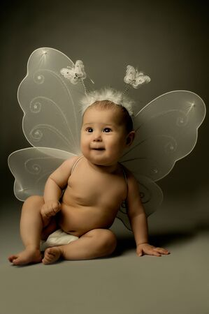 angel girl: beautiful  little kid with wings, sit and  smile on dark background