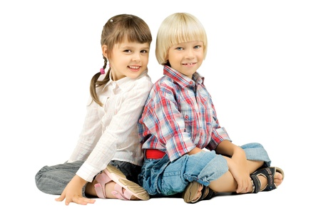 two  little children  sitting  back to back and smile, on white background, isolated Stock Photo - 8458847