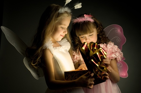examine: two little girl examine gift in fancy box, smile, on dark background