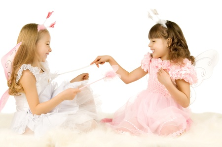 two beautiful  little girl with wings, sit and  fun game, smile,  on white background, isolated Stock Photo - 8458857
