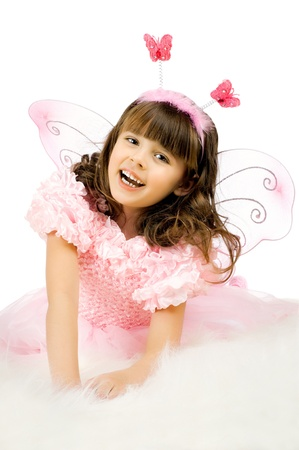 beautiful  little girl with wings, sit and  smile on white background, isolated photo