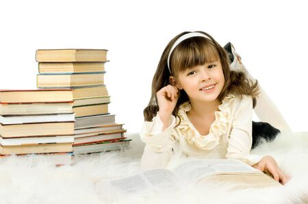 the cute little girl lie with textbook and happy smile, on white background, isolated photo