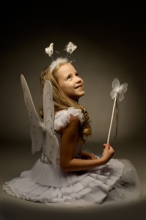 beautiful  little girl with wings, sit and  smile on dark background Stock Photo - 8458817