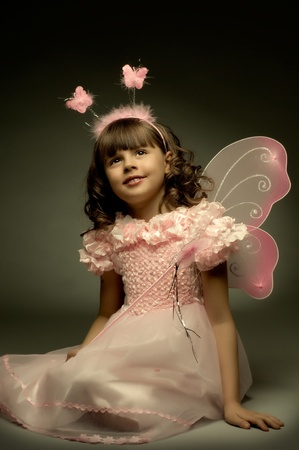 beautiful  little girl with wings, sit and  smile on dark background photo