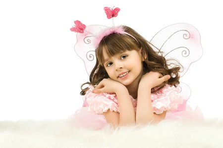 the beautiful  little girl with wings, lie and  smile on white background, isolated photo