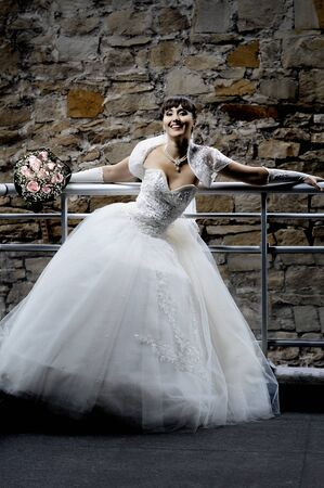 The young beautiful  happy fiancee,  with cutie wedding bouquet,  smile...