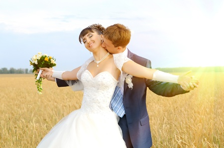 romance image: cutie happy married  couple  on nature, on wheaten field,  embrace and smile Stock Photo