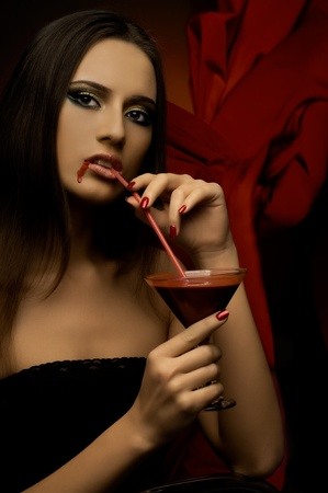 the very  pretty woman vamp, with glass and blood , sensual sexuality gaze... photo