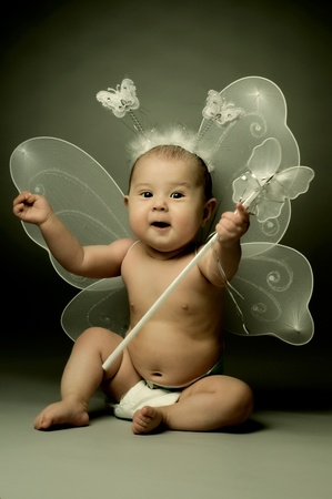 beautiful  little kid with wings, sit and  smile on dark background Stock Photo - 8874176