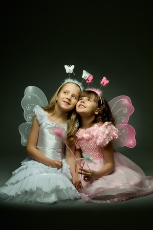 two beautiful  little girl with wings, sit and  smile on dark background Stock Photo - 8874198