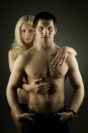 muscular handsome sexy guy with pretty woman on dark background photo