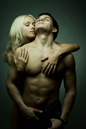 passionate embrace: muscular handsome sexy guy with pretty woman, on dark background, glamour green light Stock Photo