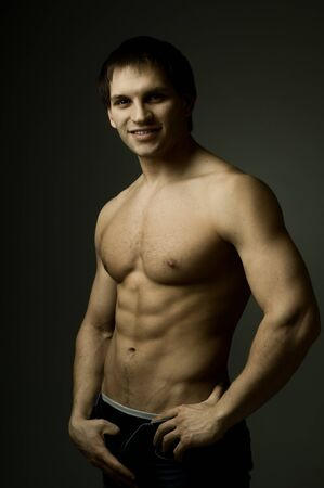 muscularity: the very muscular handsome sexy guy on dark background, smile Stock Photo