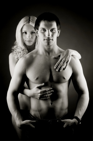 muscularity: muscular handsome sexy guy with pretty woman on dark background, gray photo
