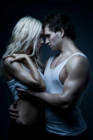 two girls hugging: muscular handsome sexy guy with pretty woman, on dark background, glamour blue light Stock Photo