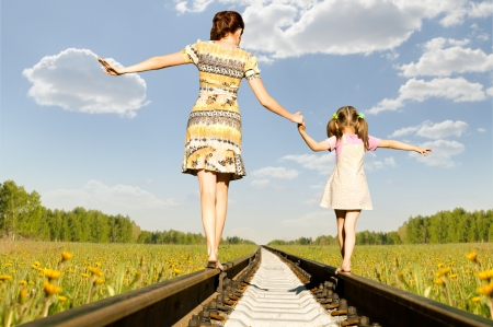 cross walk: Mother with the daughter go on rails, a back to a camera, in field, in the summer