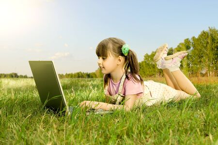 The small nice girl works on a computer, lie on a beautiful green lawn, Smile photo