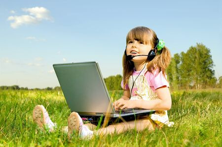 communicates: The small nice girl works on a computer, sit on a beautiful green lawn, Smile