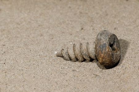 rustiness: the old rusted screw lying on  sand, close up, horizontal photo
