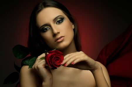the very  pretty woman on dark red background, with rose, sensual sexuality gaze... photo