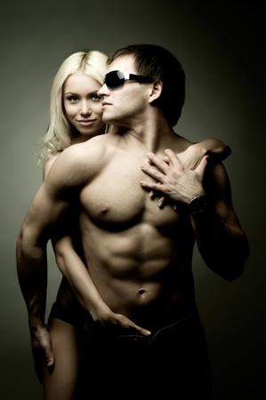 muscular handsome sexy guy with pretty woman on dark background Stock Photo - 9003160