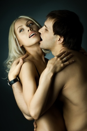 tender passion: handsome sexy guy with pretty woman,  kiss, on dark background, glamour  light