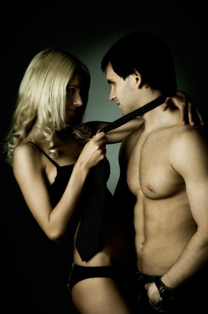 couples hug: muscular handsome sexy guy with pretty woman, on dark background, glamour  light