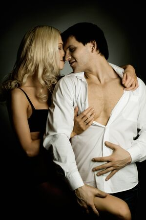 impassioned: muscular handsome sexy guy with pretty woman, on dark background, glamour  light