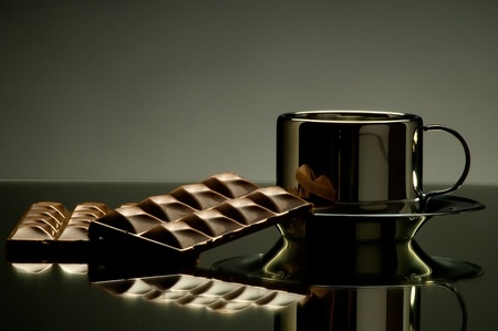 still life on mirror with polished surface steel  noggin and chocolate, on dark grey background photo