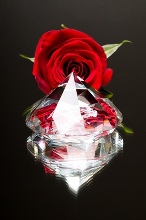 tremendous: very big diamond with red bud rose, close up, on mirror, on dark grey background Stock Photo