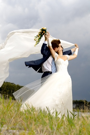 fervent: the beautiful  happy married  couple  on nature, puff wind, hot kiss